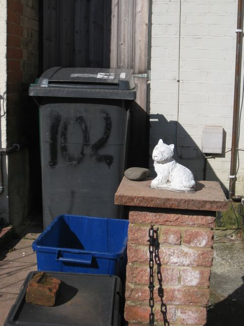 Wheelie bin and statue